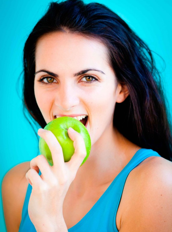 woman eating apple photo - ways to beat the bloat