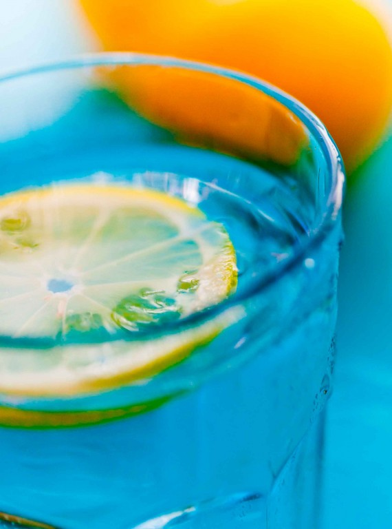 glass of water with lemon photo - ways to beat the bloat
