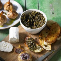 Braised new seasons garlic with tapenade toasts and fresh goats' cheese recipe