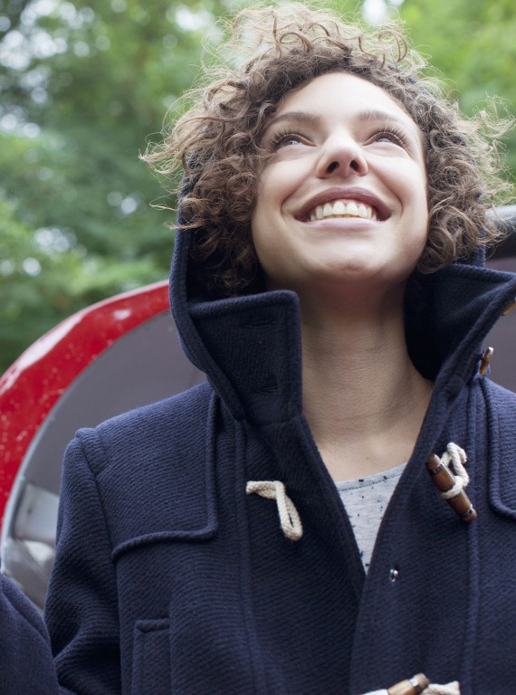 curly haired woman smiling looking up