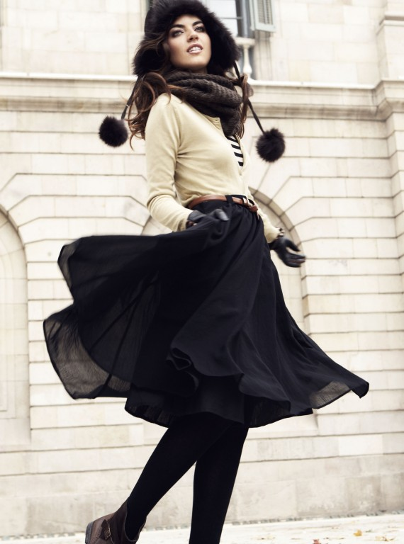 Photo of a model in a black hat and skirt and a white jumper dancing outside