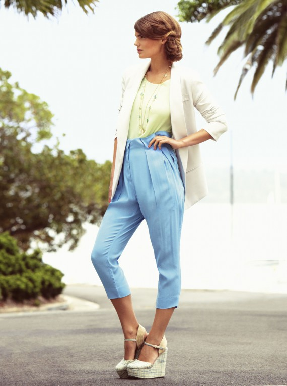 Photo of a model outside in a white jacket and blue trousers