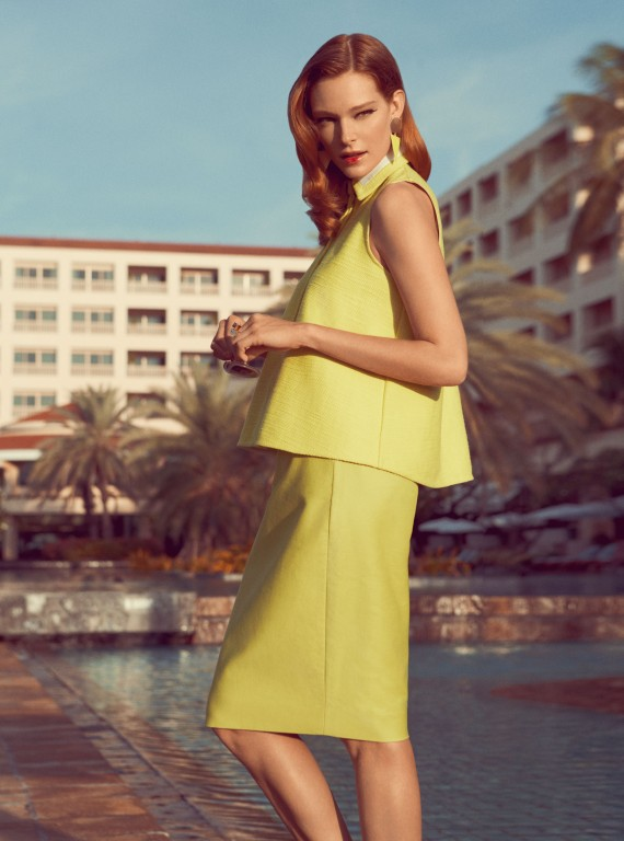 Photo of a model in a yellow dress by a pool